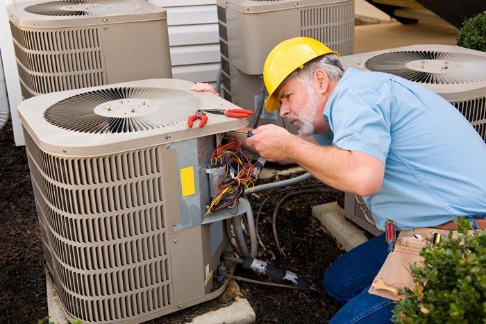 older tech examining HVAC unit