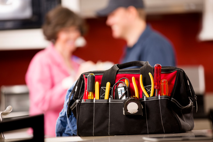 technician's tools and talking to a customer