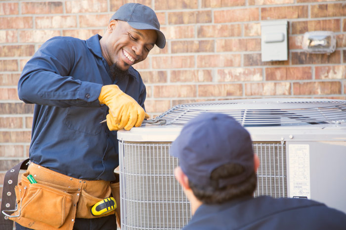 two technicians working on hvac unit
